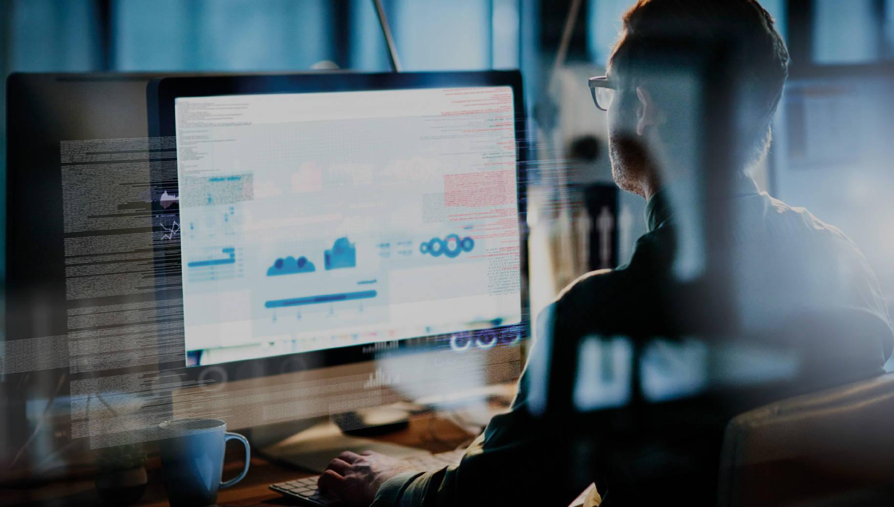 User sat at computer viewing various financial data